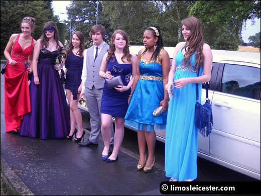 Friends stand with limousine prior to leaving for the school prom