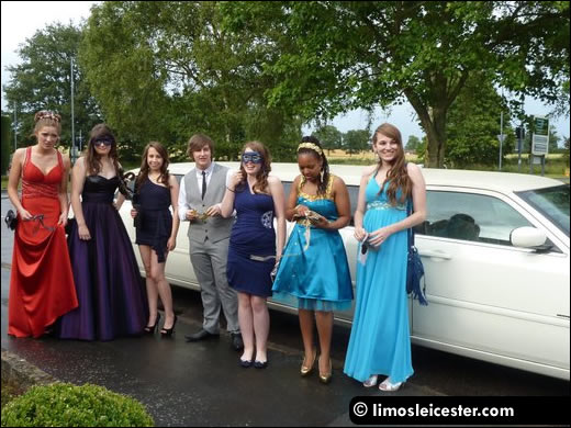 Promgoers stand with limousine